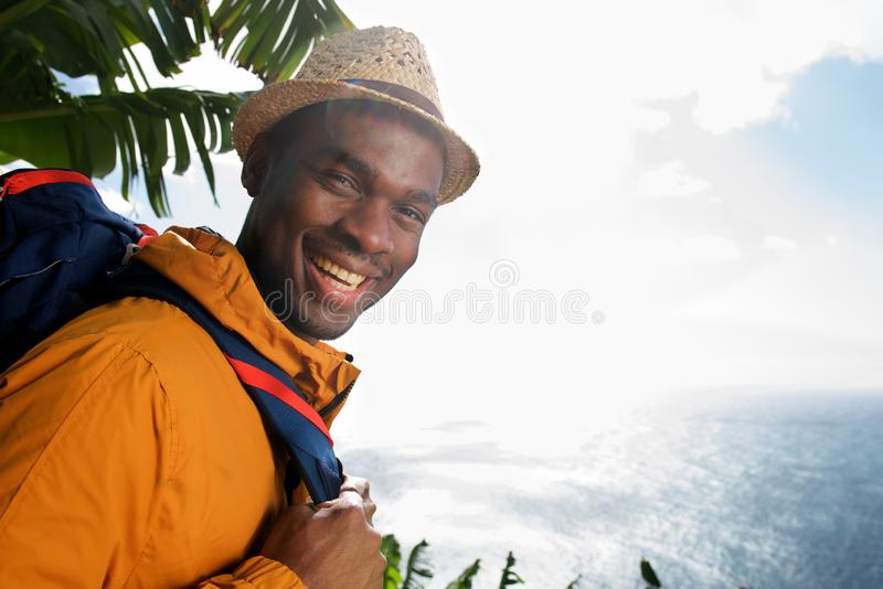 Ritratto laterale del viaggiatore maschio felice con il mare facente una pausa dello zaino fotografia stock libera da diritti