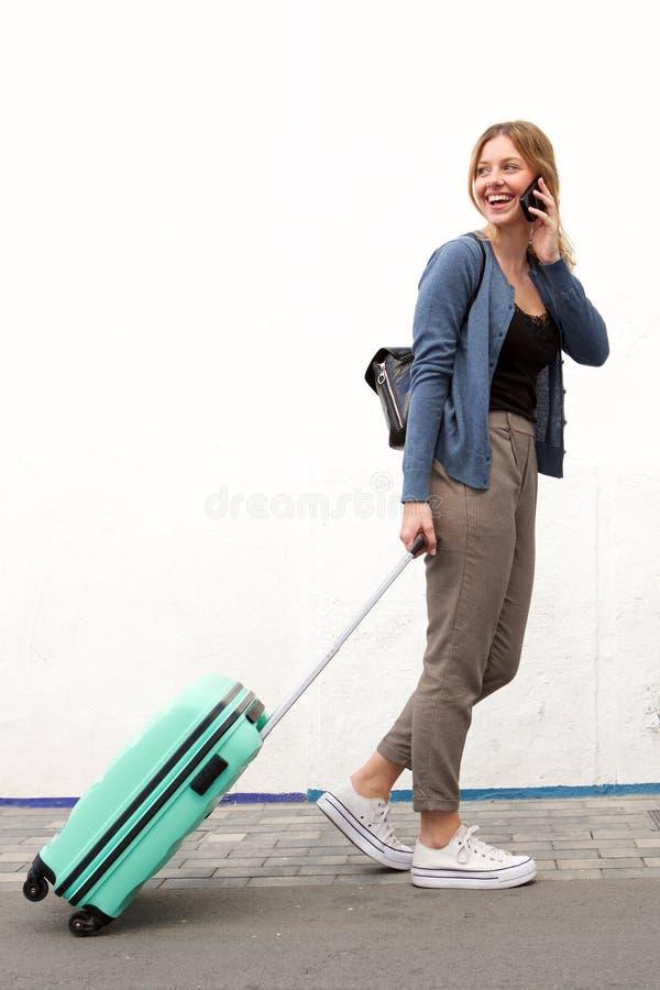 Ritratto laterale della donna di viaggio dei giovani che cammina e che parla con il telefono cellulare contro la parete bianca fotografia stock