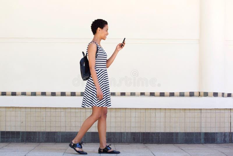Ritratto laterale della giovane donna che cammina sopra con il cellulare e la borsa fotografie stock