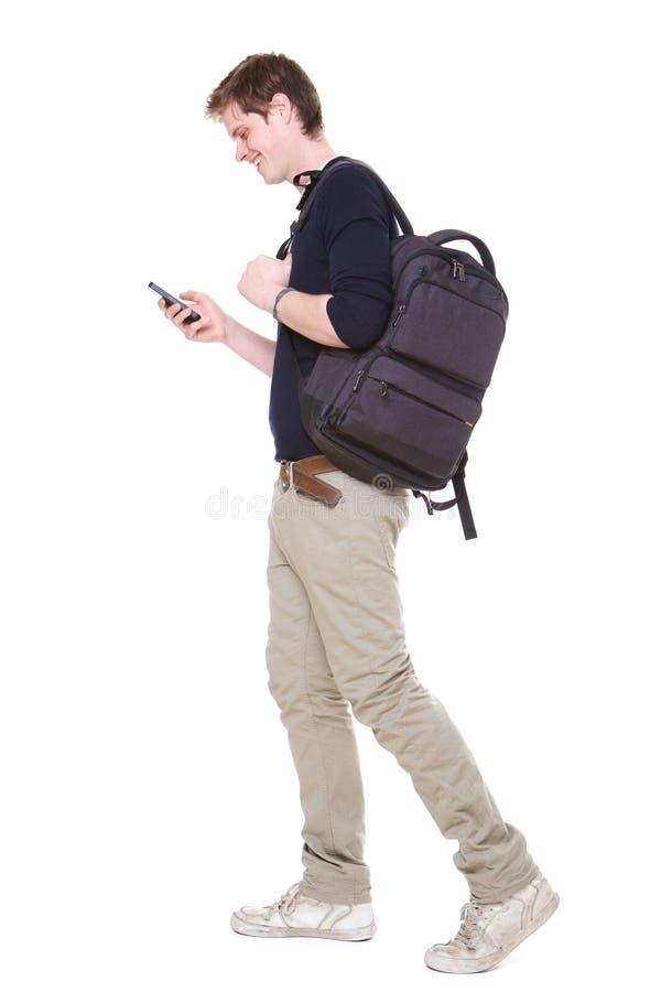 Ritratto laterale integrale di giovane studente maschio che cammina sul fondo bianco isolato con la borsa ed il telefono cellular fotografie stock libere da diritti