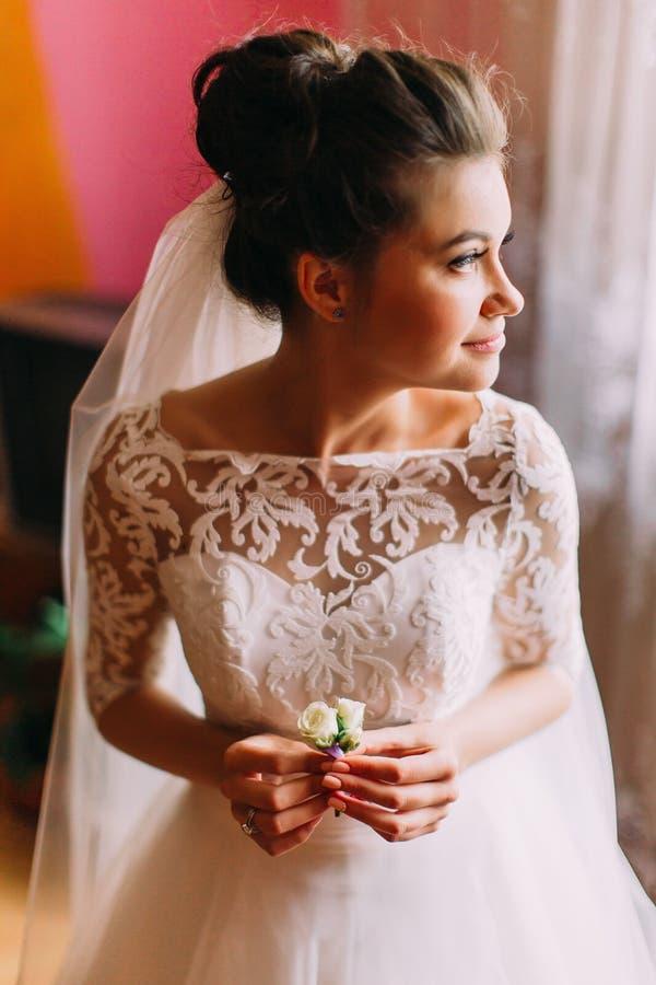 Ritratto laterale sensibile di bello holdign della sposa il boutonniere e guardare da parte immagine stock