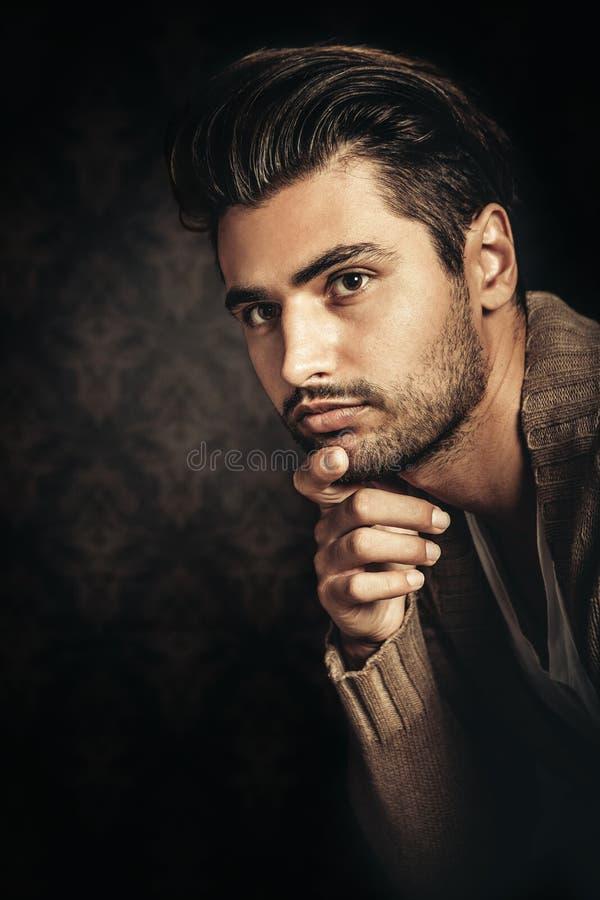 Ritratto leggero scuro di giovane uomo bello, mano sotto il suo mento immagini stock