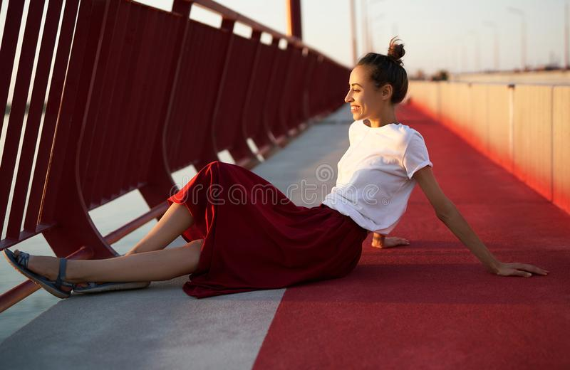 Ritratto luminoso di stile di vita di estate di giovane donna graziosa in gonna rossa e maglietta bianca, sedentesi su un pavimen fotografia stock libera da diritti