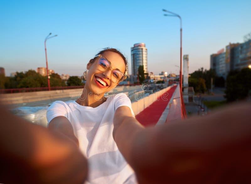 Ritratto luminoso di stile di vita di estate di giovane donna graziosa in occhiali, gonna rossa e maglietta bianca, prendenti un  immagini stock libere da diritti
