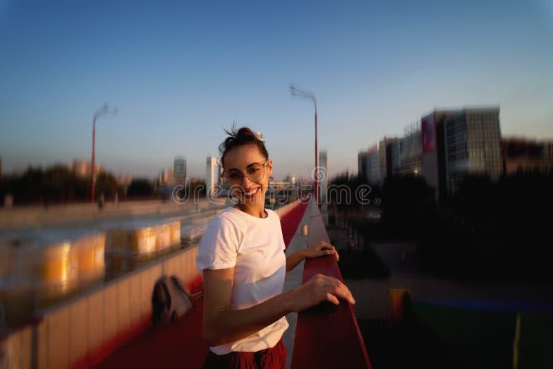 Ritratto luminoso di stile di vita di estate di giovane donna graziosa in occhiali, gonna rossa e maglietta bianca, stanti sul lu immagini stock
