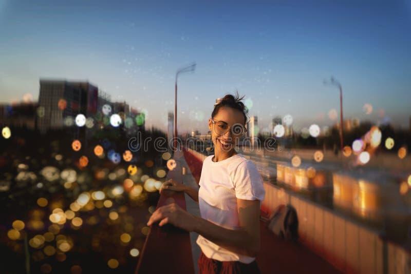 Ritratto luminoso di stile di vita di estate di giovane donna graziosa in occhiali, gonna rossa e maglietta bianca, stanti sul lu fotografia stock