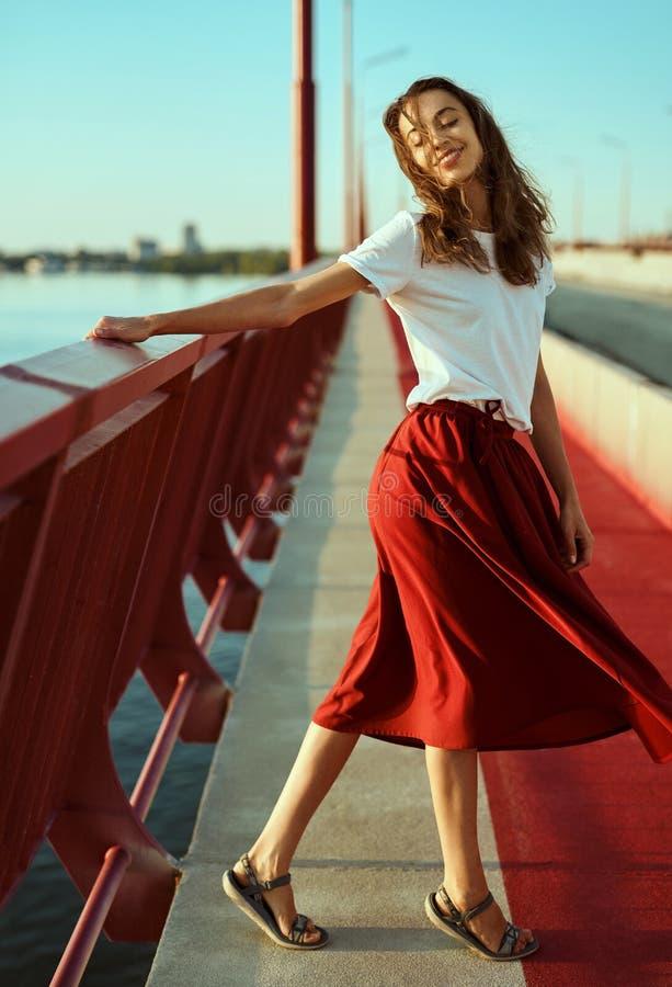 Ritratto luminoso di stile di vita di giovane donna graziosa in gonna rossa e maglietta bianca, posare, camminante su un paviment fotografia stock