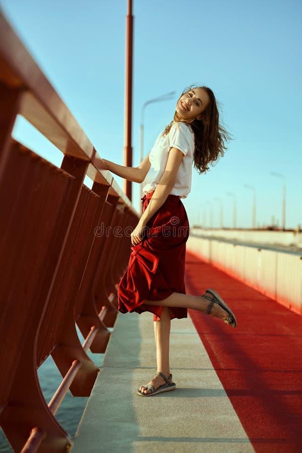 Ritratto luminoso di stile di vita di giovane donna graziosa in gonna rossa e maglietta bianca, posare, stante su un pavimento ro fotografie stock libere da diritti