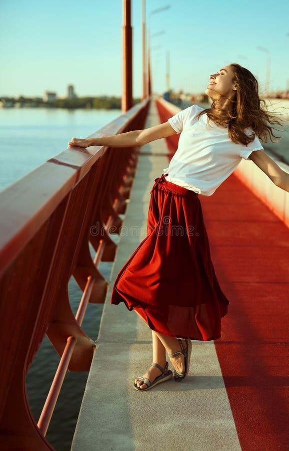 Ritratto luminoso di stile di vita di giovane donna graziosa in gonna rossa e maglietta bianca, posare, stante su un pavimento ro immagini stock libere da diritti