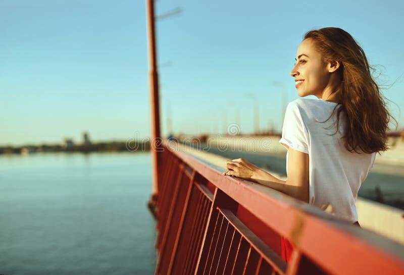 Ritratto luminoso di stile di vita di giovane donna graziosa in gonna rossa e maglietta bianca, posare, stante su un pavimento ro fotografia stock