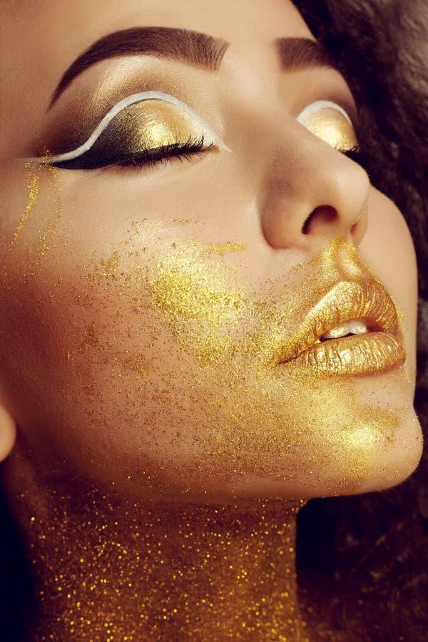 Ritratto magico della ragazza in oro Trucco dorato immagini stock