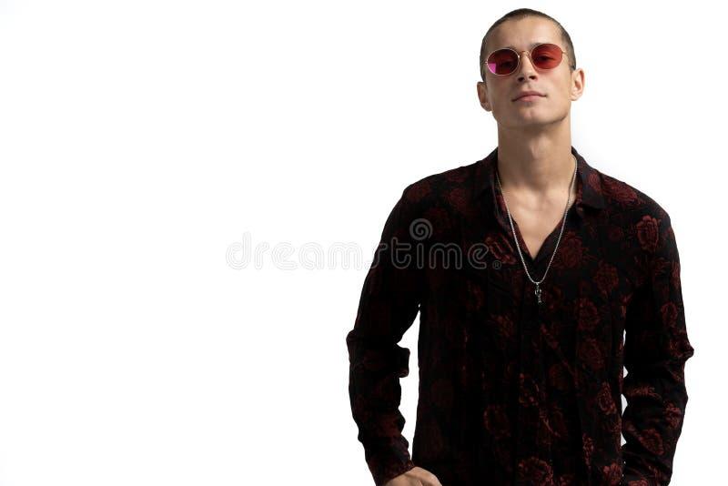 Ritratto mezzo di lunghezza di giovane enterpreneur maschio sicuro e riuscito in camicia nera ed occhiali da sole rossi, con brev fotografia stock libera da diritti