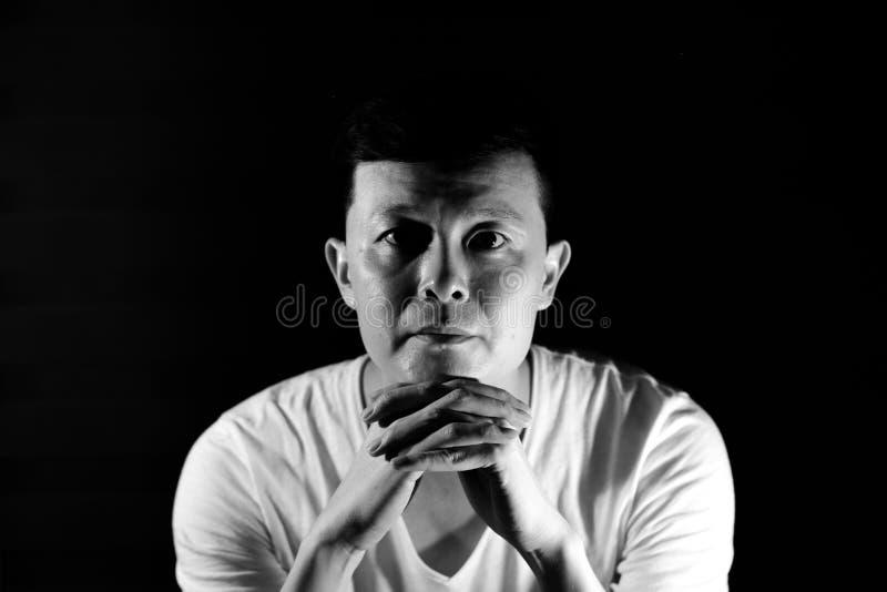 Ritratto monocromatico dell'uomo asiatico che esamina la macchina fotografica con smil immagine stock libera da diritti