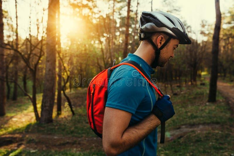 Ritratto nel profilo di giovane ciclista barbuto bello dell'uomo che indossa casco protettivo, maglietta blu e zaino rosso, guard fotografia stock libera da diritti