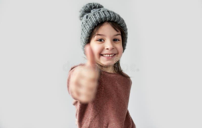 Ritratto orizzontale della bambina sorridente felice nel cappello grigio caldo di inverno, maglione d'uso e di mostra pollice su, immagine stock