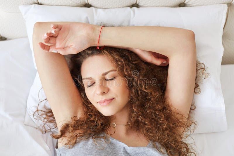Ritratto orizzontale della femmina sveglia sonnolenta con capelli ricci, richieste immagine stock libera da diritti