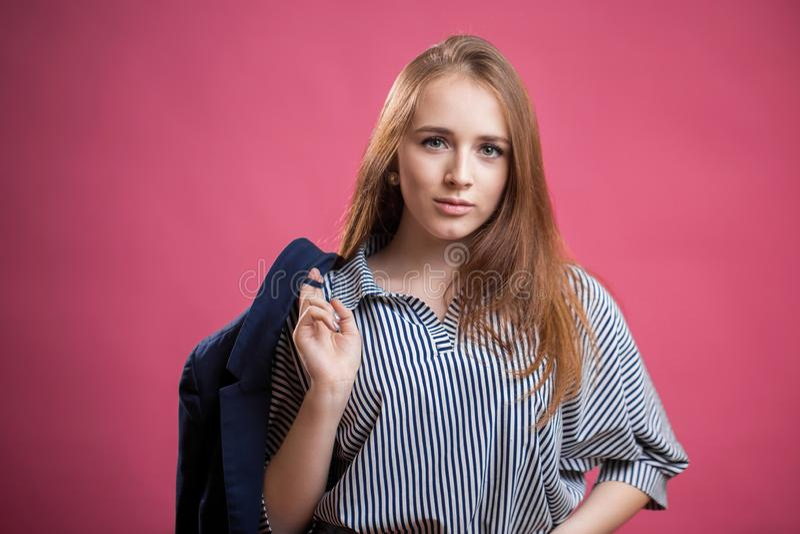 Ritratto orizzontale di bella ragazza dai capelli rossi dello studente su un fondo rosa Una giovane donna porta una blusa a stris fotografie stock libere da diritti