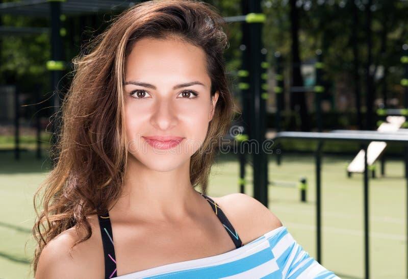 Ritratto orizzontale di giovane bella donna su un campo da giuoco della città immagine stock