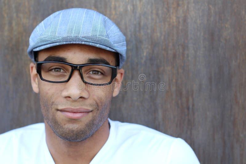 Ritratto orizzontale di giovane uomo africano bello che smicing sul fondo marrone strutturato della parete immagine stock