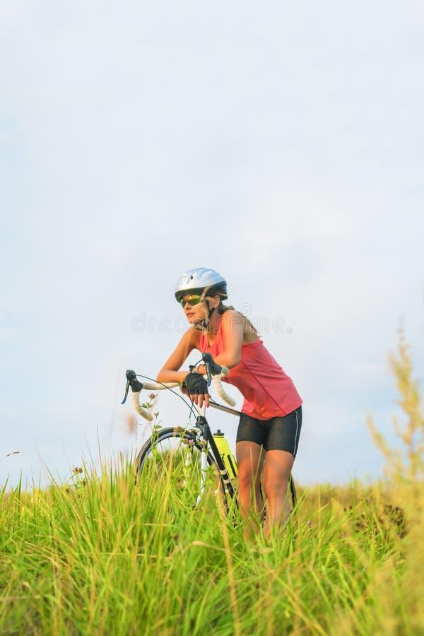 Ritratto piacevole di giovane atleta femminile di sport che riposa fuori. immagini stock