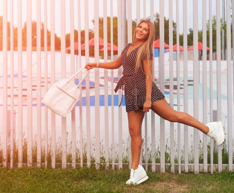 Ritratto pieno di sole Bellezza con capelli lunghi con una borsa di sport che posa su una sera calda Avere divertimento immagini stock
