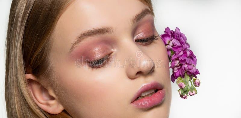 Ritratto potato della ragazza con gli occhi chiusi, trucco luminoso, fiori porpora arricciati in capelli Salute e bellezza natura fotografia stock