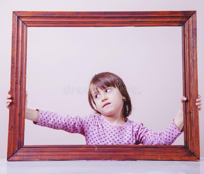 Ritratto psicologico delle regole d'estensione della ragazza sveglia del piccolo bambino oltre la struttura Concetto di libert? fotografie stock libere da diritti