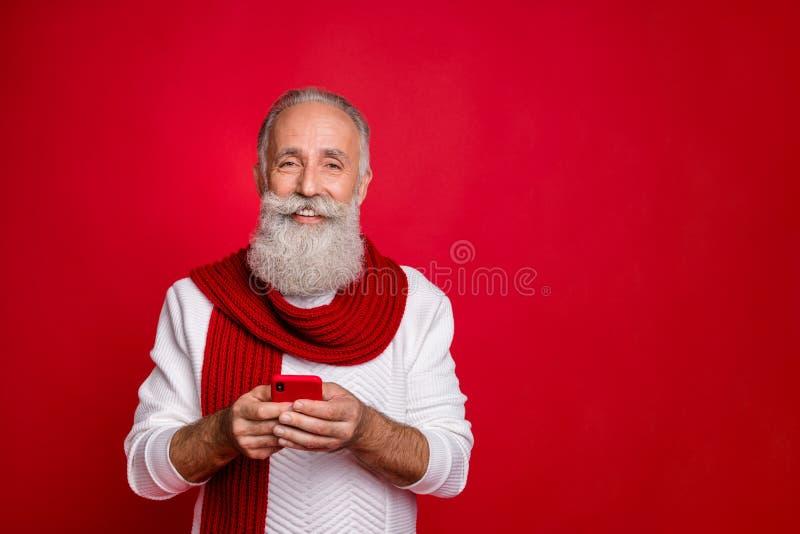 Ritratto ravvicinato del suo simpatico allegro e allegro uomo dai capelli grigi che tiene a mani nude usando la cellula immagini stock libere da diritti