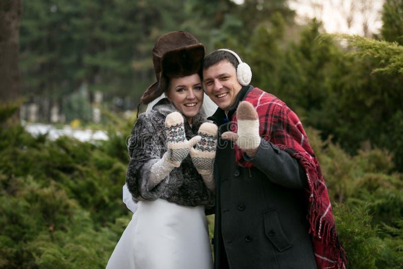 Ritratto recentemente della coppia sposata in sciarpe e cappelli che posano a w immagini stock libere da diritti