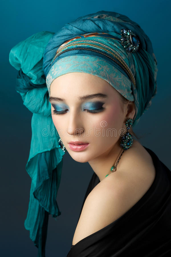 Ritratto romantico della giovane donna in un turbante del turchese su un damerino fotografia stock libera da diritti