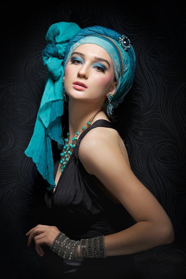 Ritratto romantico della giovane donna in un turbante del turchese su un damerino fotografie stock