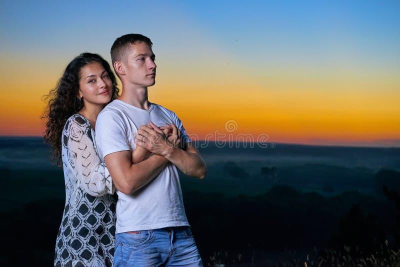 Ritratto romantico delle coppie al tramonto su paesaggio all'aperto e bello e sul cielo giallo luminoso, concetto di tenerezza di fotografie stock