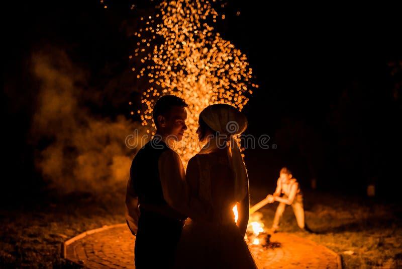 Ritratto romantico di belle persone appena sposate alla notte ai precedenti delle fiamme del fuoco bruciante fotografie stock libere da diritti