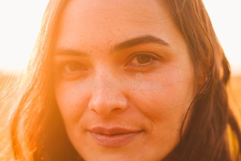 Ritratto schietto di bella giovane donna con le lentiggini vicine sull'esterno di estate immagini stock