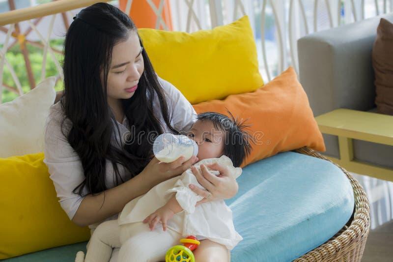 Ritratto schietto di stile di vita di giovane donna cinese asiatica felice e dolce che alimenta la sua bella neonata con la botti immagine stock libera da diritti