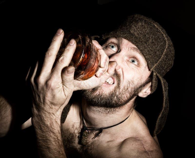 Ritratto scuro dell'uomo barbuto sinistro diabolico spaventoso con sorrisetto, tenente una bottiglia del cognac uomo russo sconos fotografia stock libera da diritti