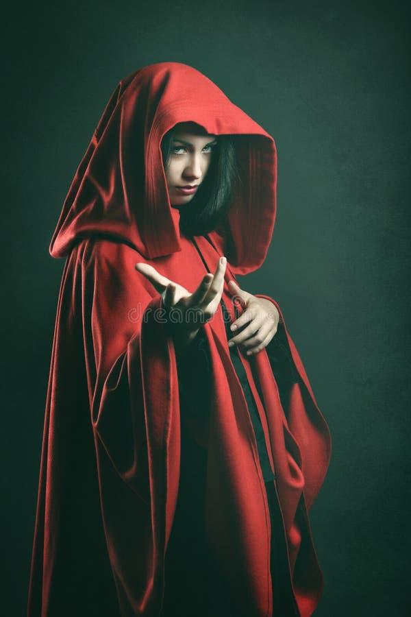 Ritratto scuro di bella donna con il mantello rosso immagine stock libera da diritti