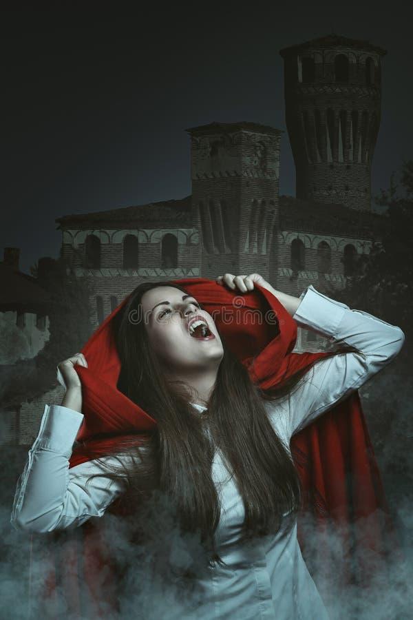 Ritratto scuro di un vampiro incappucciato rosso fotografie stock libere da diritti