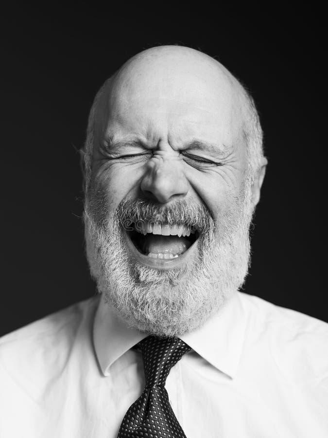Ritratto senior allegro dell'uomo d'affari su fondo nero immagini stock libere da diritti