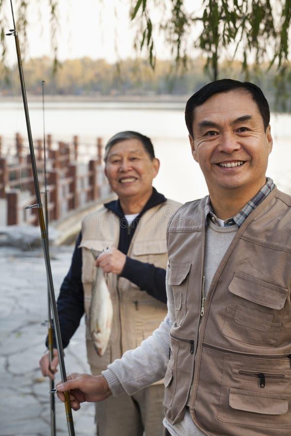 Ritratto senior degli amici mentre pescando in un lago immagine stock libera da diritti