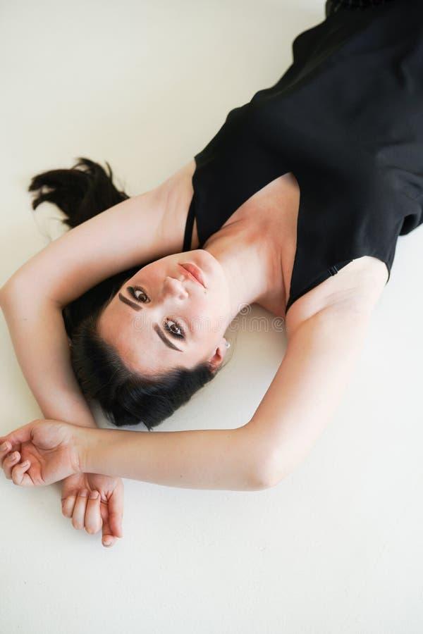 Ritratto sensuale della donna che mette su fondo bianco in biancheria intima nera fotografia stock