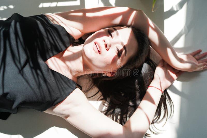 Ritratto sensuale della donna che mette su fondo soleggiato bianco in biancheria intima nera immagini stock libere da diritti