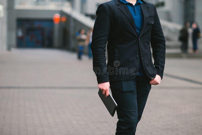 Ritratto senza testa di un uomo d'affari che tiene un computer della compressa sui precedenti della città fotografia stock