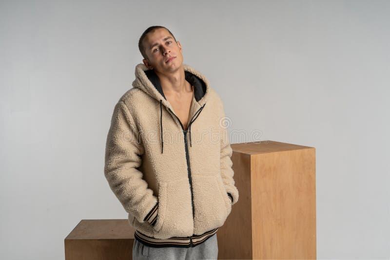 Ritratto serio di un giovane bello con breve taglio di capelli che posa vicino ai cubi di legno fotografia stock
