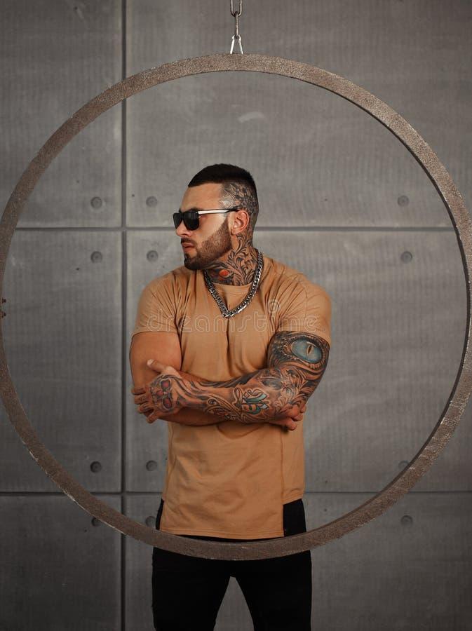Ritratto sexy del primo piano del modello maschio bello elegante con il tatuaggio di modo e di una barba nera che sta e che posa  immagini stock libere da diritti