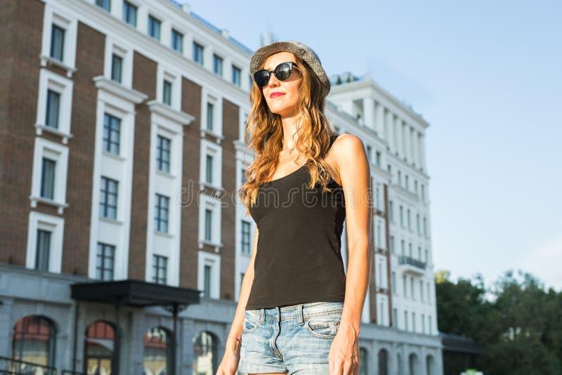 Ritratto soleggiato di modo di stile di vita di estate di giovane donna alla moda che cammina sulla via, attrezzatura d'avanguard immagini stock