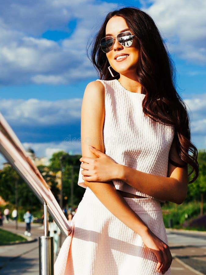 Ritratto soleggiato luminoso di una ragazza asiatica in attrezzatura ed occhiali da sole di estate su una via della città fotografia stock