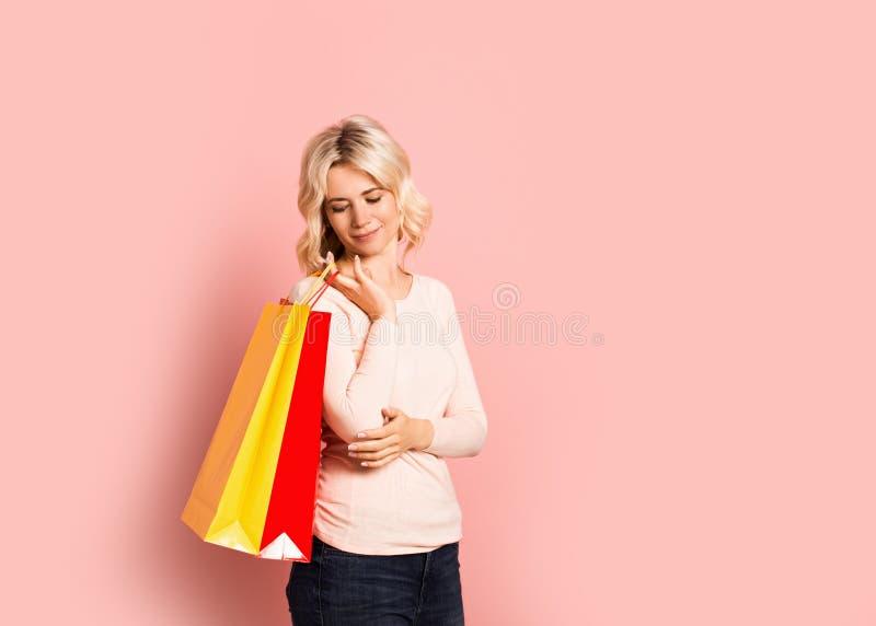 Ritratto sorridente attraente adulto della donna bionda bello, ragazza caucasica con i sacchetti della spesa su fondo rosa fotografie stock libere da diritti