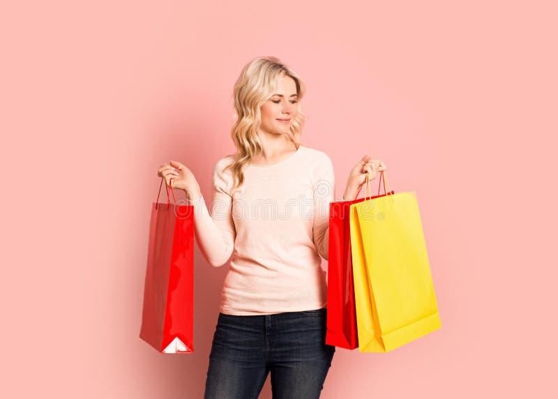 Ritratto sorridente attraente adulto della donna bionda bello, ragazza caucasica con i sacchetti della spesa su fondo rosa immagini stock libere da diritti
