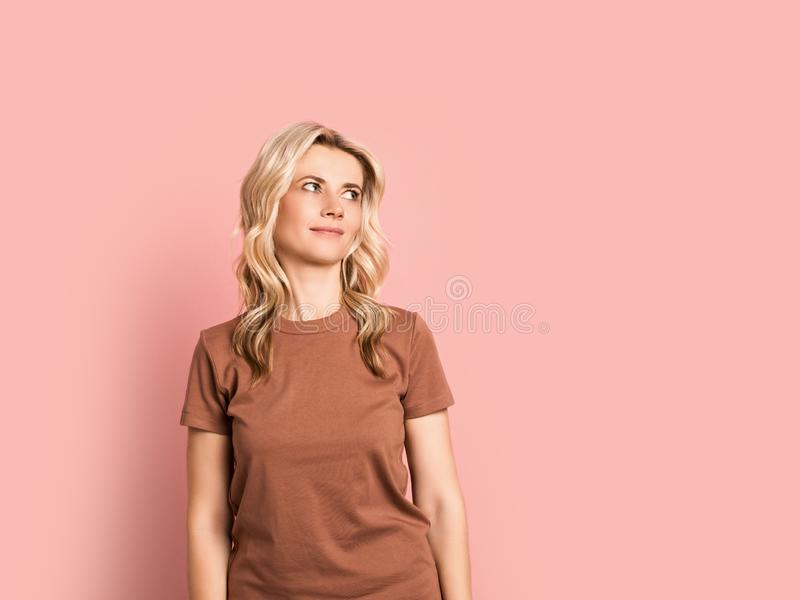Ritratto sorridente attraente adulto della donna bionda bello, ragazza caucasica su fondo rosa immagini stock